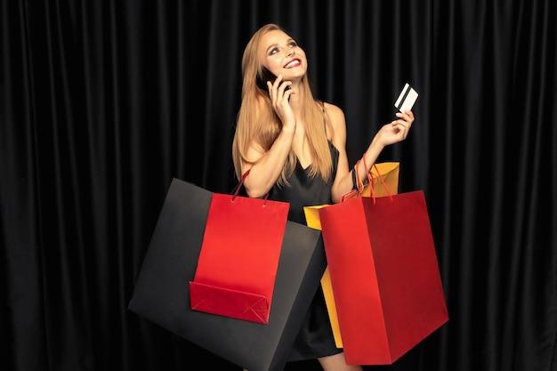 Jonge vrouw die in kleding op zwarte muur winkelt Gratis Foto