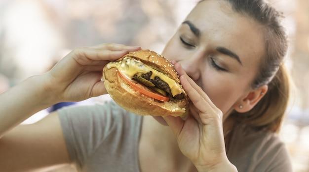 Jonge vrouw die in koffie smakelijke sandwich eet Gratis Foto