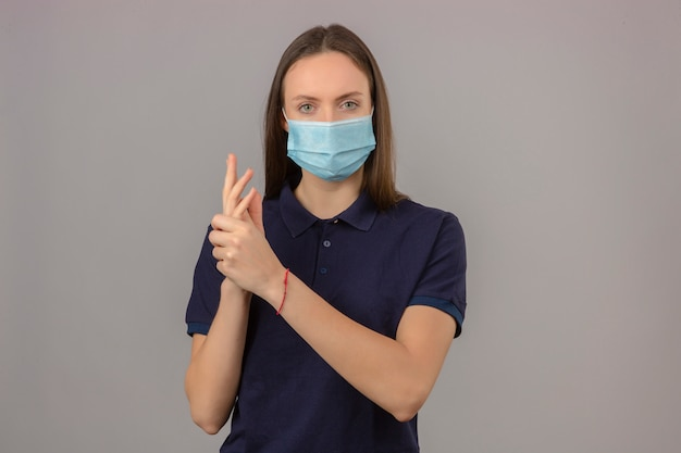 Jonge vrouw die in marinepolooverhemd en medisch beschermend masker schone handen tonen die camera bekijken die zich op lichtgrijze achtergrond bevinden Gratis Foto