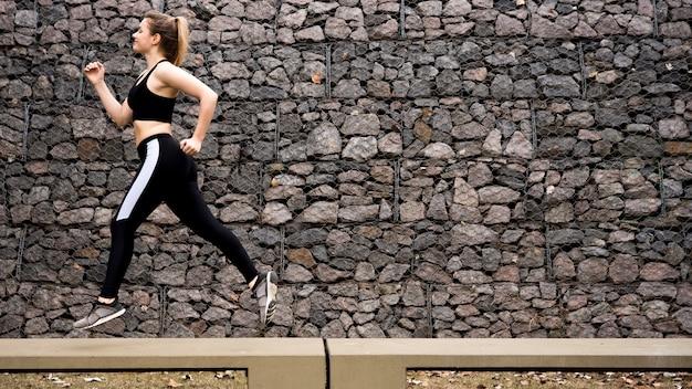 Jonge vrouw die in openlucht met sportkleding loopt Gratis Foto