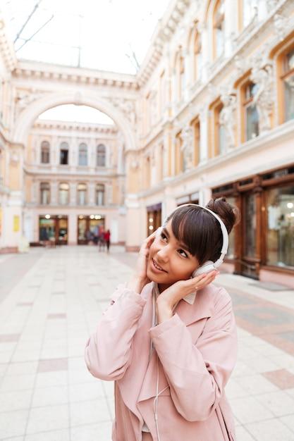 Jonge vrouw die in roze laag aan muziek met buiten hoofdtelefoons luisteren Gratis Foto
