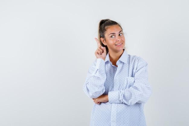 Jonge vrouw die in wit overhemd wijsvinger in eureka-gebaar opheft en verstandig kijkt Gratis Foto