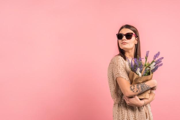 Jonge vrouw die in zonnebril zak met bloemen houdt Gratis Foto