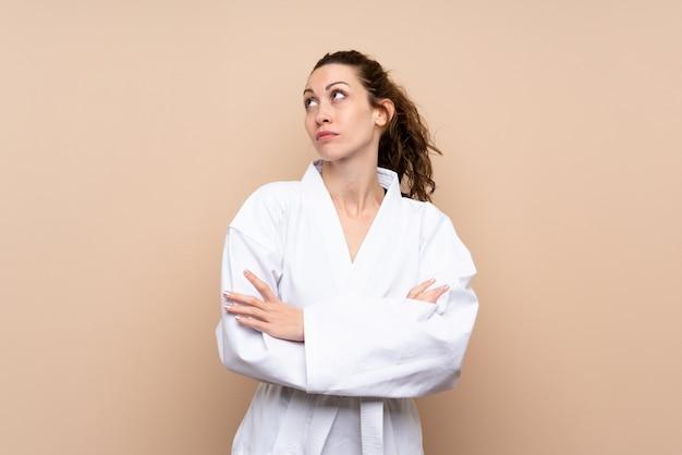 Jonge vrouw die karate doet die twijfelgebaar maken terwijl het opheffen van de schouders Premium Foto