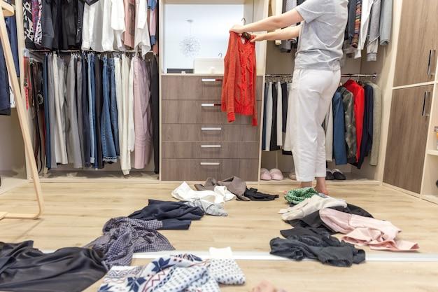 Jonge vrouw die kleren in gang in kast werpt, knoeit in garderobe en kleedkamer Premium Foto