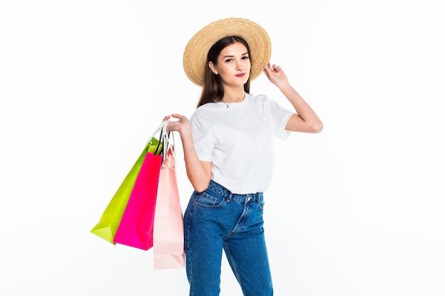 Jonge vrouw die kleurrijke zakken houdt die op witte muur worden geïsoleerd Gratis Foto