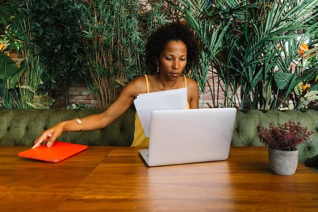 Jonge vrouw die laptop holdingsdocument en digitale tablet op houten lijst bekijken Gratis Foto
