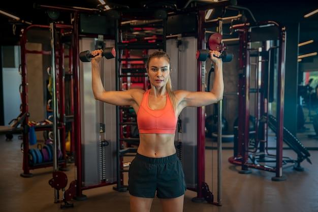 Jonge vrouw die met domoren uitoefenen om bicepsen en schouders in gymnastiek te versterken Premium Foto