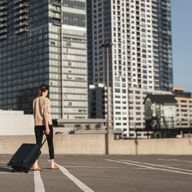 Jonge vrouw die met een koffer in de stad loopt Gratis Foto