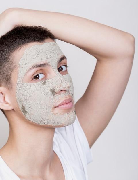 Jonge vrouw die met gezichtsmasker de camera bekijkt Gratis Foto