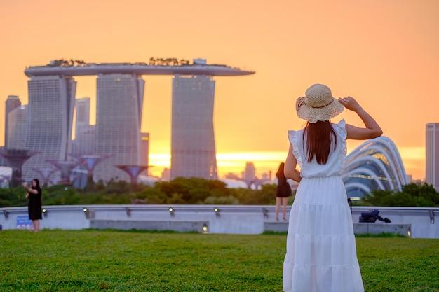 Jonge vrouw die met hoed bij zonsondergang, gelukkig aziatisch reizigersbezoek reist in stad de van de binnenstad van singapore. oriëntatiepunt en populair voor toeristenaantrekkelijkheden. azië reizen concept Premium Foto