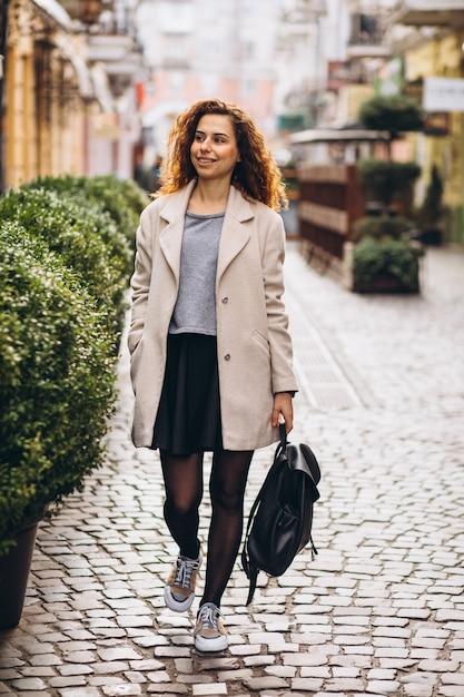 Jonge vrouw die met krullend haar bij een koffiestraat loopt Gratis Foto