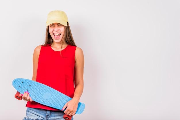Jonge vrouw die met skateboard op witte achtergrond lacht Gratis Foto