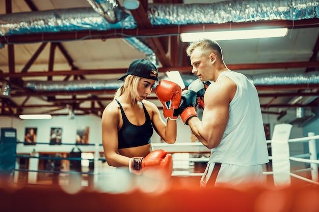 Jonge vrouw die met trainer bij het in dozen doen en zelfverdedigingsles uitoefenen Premium Foto