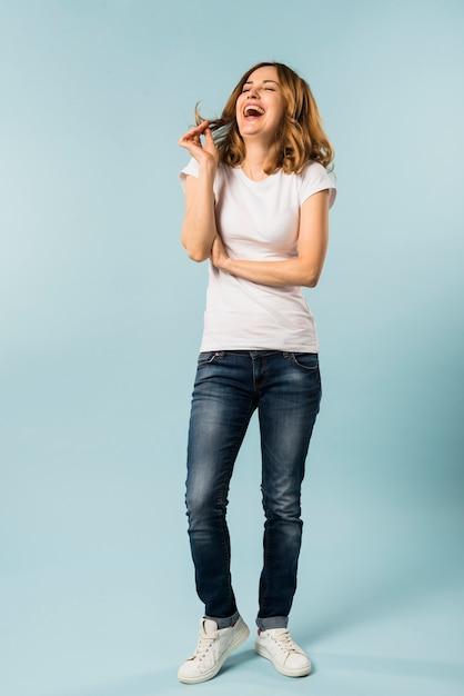 Jonge vrouw die met vreugde tegen blauwe achtergrond lacht Gratis Foto