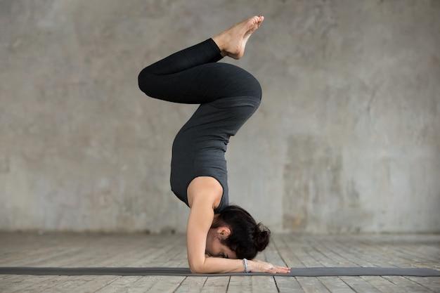 Jonge vrouw die oefening pincha mayurasana doet Gratis Foto