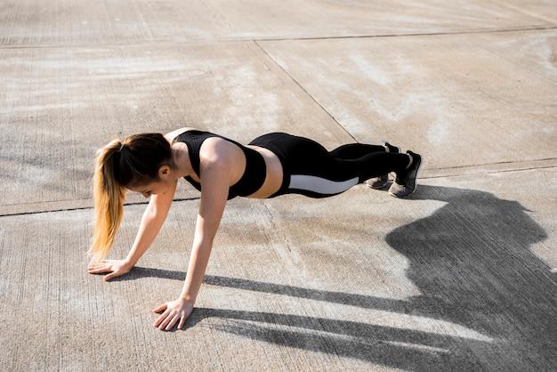 Jonge vrouw die oefeningen doet bij de straat Gratis Foto