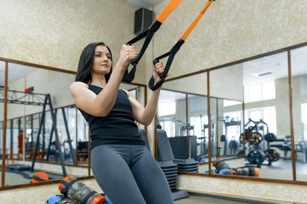 Jonge vrouw die oefeningen doet die het riemensysteem gebruiken Premium Foto