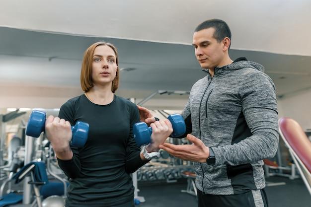 Jonge vrouw die oefeningen met persoonlijke instructeur in gymnastiek doet. Premium Foto