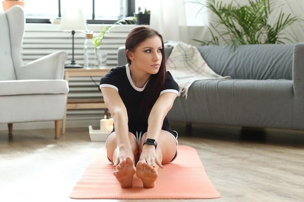 Jonge vrouw die oefeningen thuis doet Gratis Foto