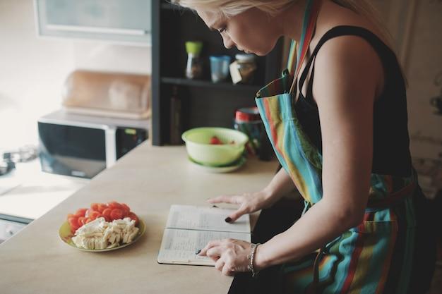 Jonge vrouw die omhoog in een receptenboek kijkt Gratis Foto