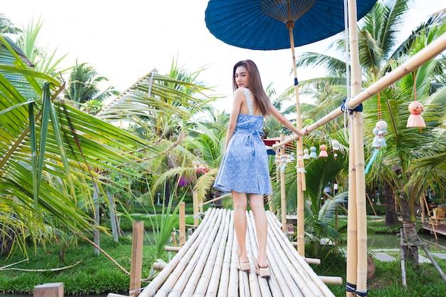 Jonge vrouw die op bamboebrug loopt Gratis Foto