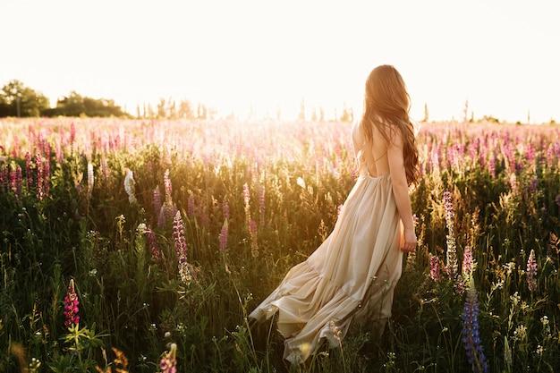 Jonge vrouw die op bloemgebied bij zonsondergang op achtergrond loopt. Gratis Foto