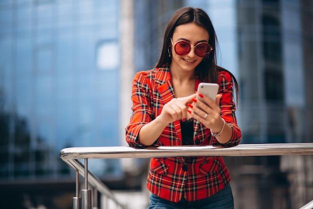 Jonge vrouw die op de telefoon door het bureaucentrum spreekt Gratis Foto