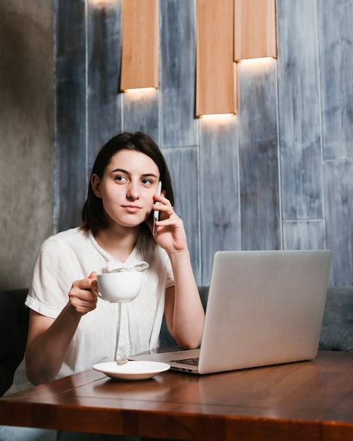 Jonge vrouw die op de telefoon in het bureau spreekt Gratis Foto