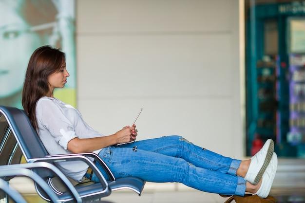 Jonge vrouw die op de telefoon spreekt terwijl het wachten instappen Premium Foto