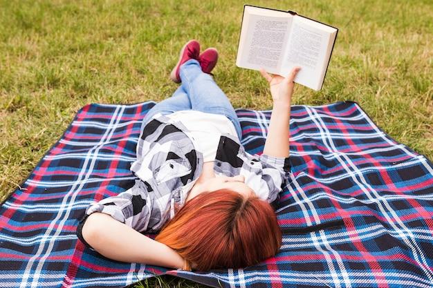 Jonge vrouw die op dekenlezingsboek ligt Gratis Foto