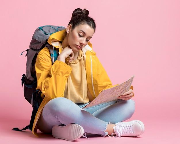 Jonge vrouw die op een kaart zoekt Gratis Foto