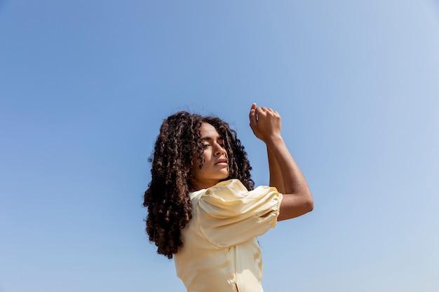 Jonge vrouw die op hemelachtergrond danst Gratis Foto