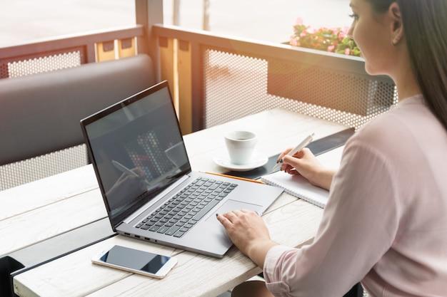 Jonge vrouw die op laptop werkt en schrijft Premium Foto