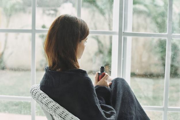 Jonge vrouw die op leunstoel thuis door het venster rust Premium Foto
