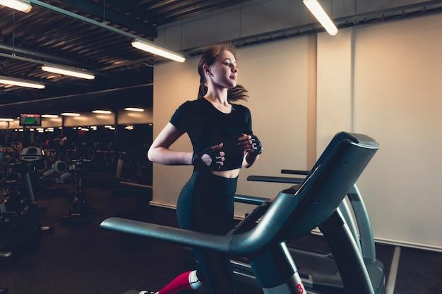 Jonge vrouw die op tredmolen bij gymnastiek loopt Premium Foto