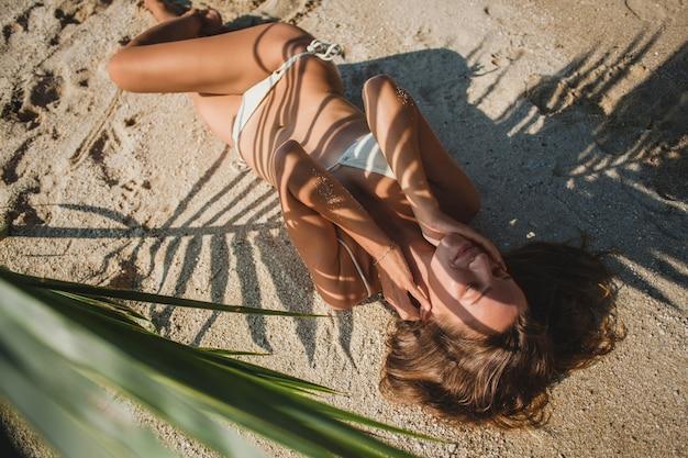 Jonge vrouw die op zandstrand onder palmblad legt Gratis Foto