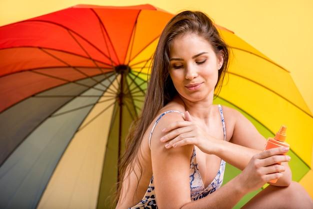 Jonge vrouw die op zonnescherm zet Gratis Foto