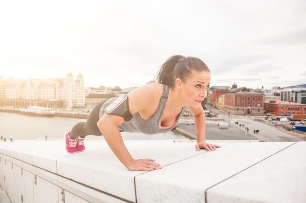Jonge vrouw die opdrukoefeningenoefeningen doet Premium Foto