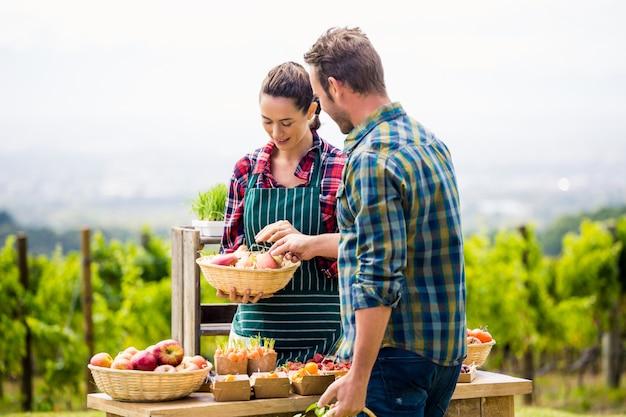 Jonge vrouw die organische groenten verkoopt aan de mens bij landbouwbedrijf Premium Foto