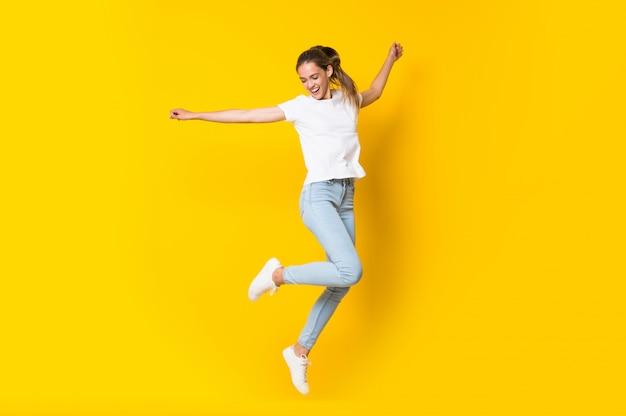 Jonge vrouw die over geïsoleerde gele muur springt Premium Foto