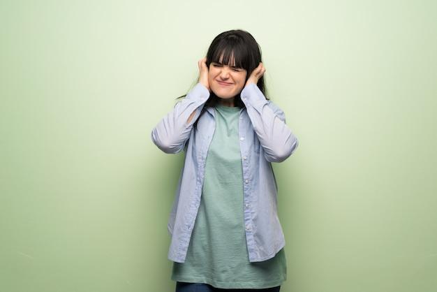 Jonge vrouw die over groene muur oren behandelt met handen. gefrustreerde uitdrukking Premium Foto