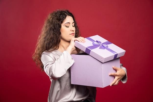 Jonge vrouw die paarse giftdoos controleert. Gratis Foto