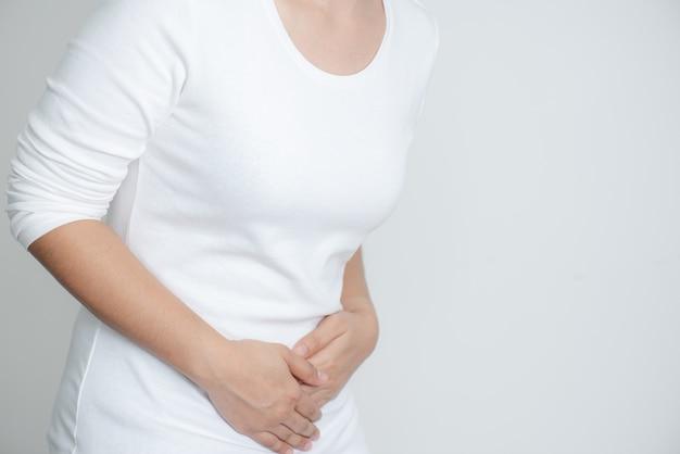 Jonge vrouw die pijnlijke buikpijn op witte achtergrond heeft Premium Foto