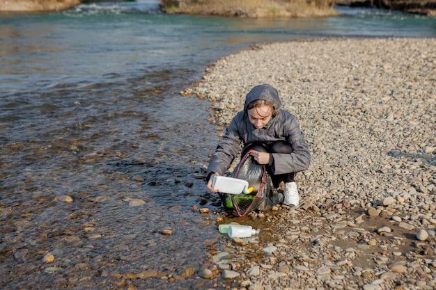 Jonge vrouw die plastic afval van het strand verzamelt en het in zwarte plastic zakken voor kringloop zet. reiniging en recycling concept. Premium Foto