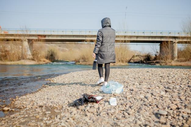 Jonge vrouw die plastic afval van het strand verzamelt en in zwarte plastic zakken doet Premium Foto