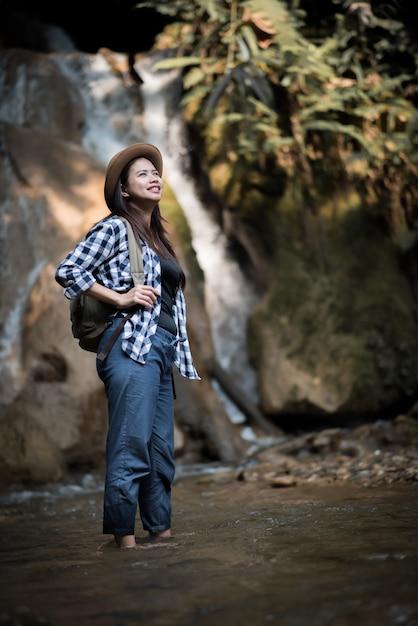 Jonge vrouw die pret heeft onder watervallen in het bos Premium Foto