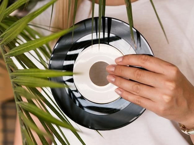 Jonge vrouw die retro vinylverslag houdt dichtbij installatie Gratis Foto