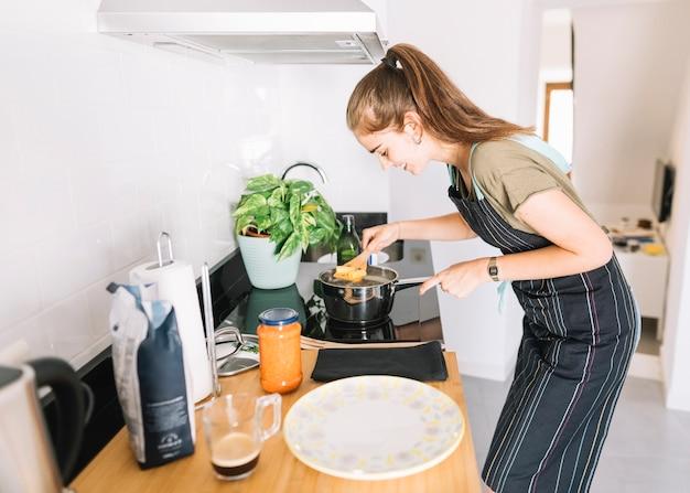 Jonge vrouw die rigatonideegwaren in de sauspan over het elektrische fornuis koken Gratis Foto