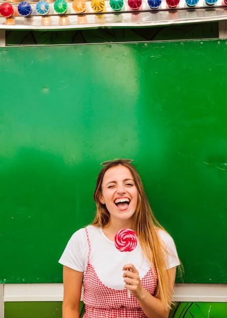 Jonge vrouw die rode lolly in haar hand het lachen houdt Gratis Foto